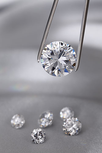 Tweezers holding a large diamond with smaller diamonds in the background