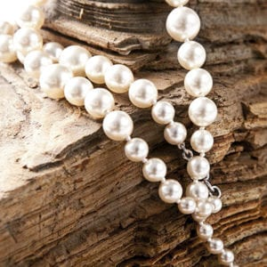 Close up of a pearl necklace draped over a piece of stone