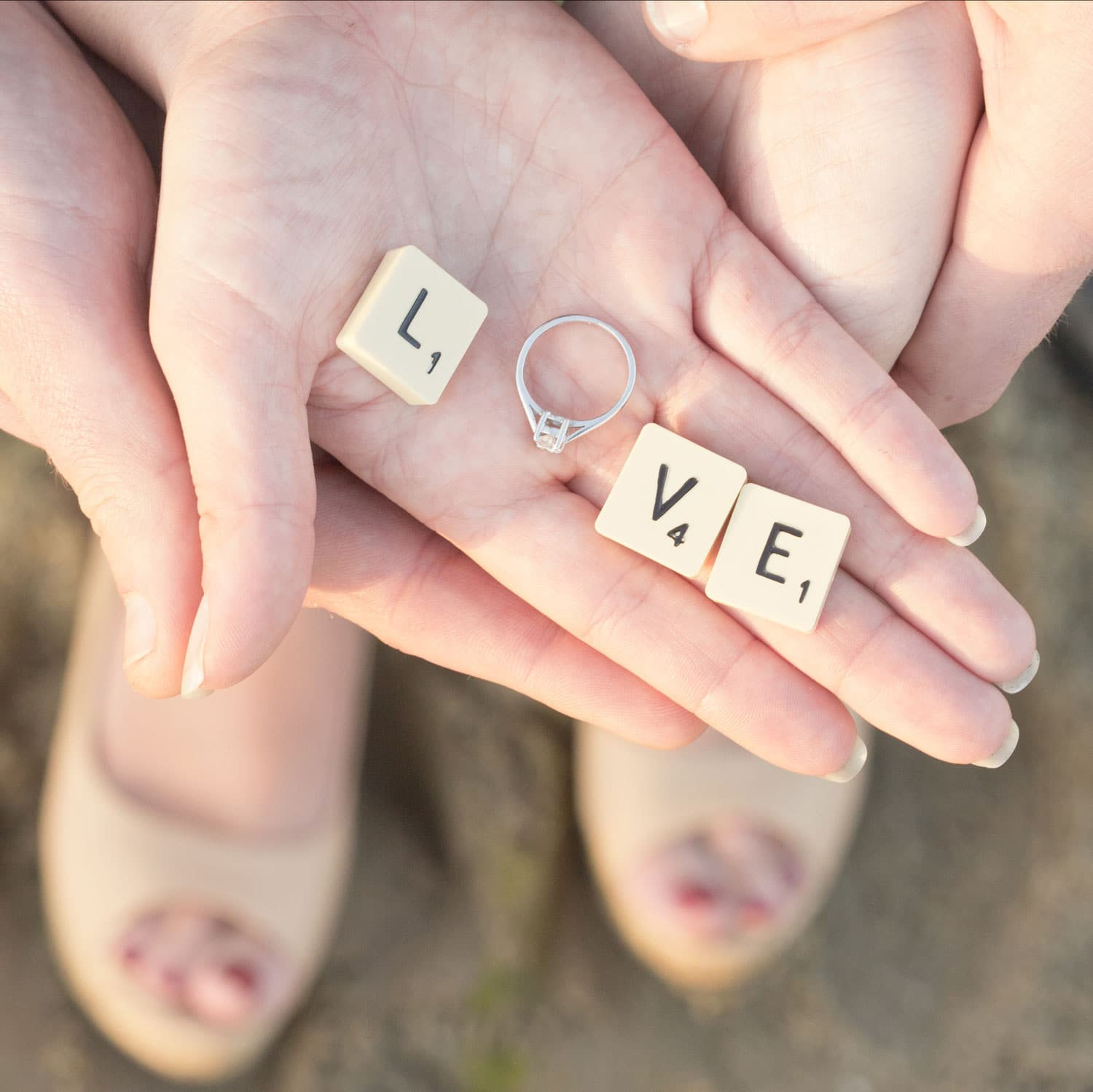 Woman holding Scrabble pieces and a ring that spell out love