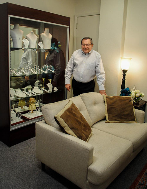 Picture of Seymour Wolchuk standing next to a jewelry case with a hand on a couch