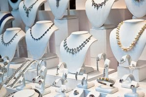 Several necklaces and other jewelry on pedestals in a row