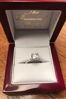 a ring box with a diamond ring and the diamond broker written on the box